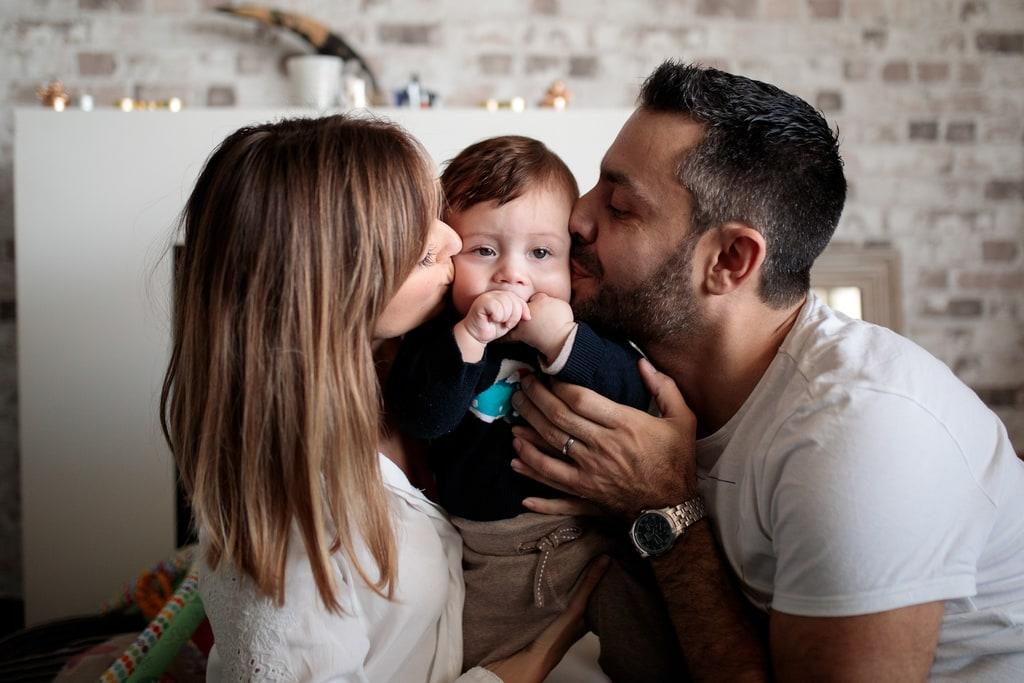 papa et maman qui embrasse leur bébé