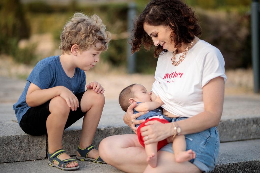 maman qui allaite son bébé sous le regard de son grand frère