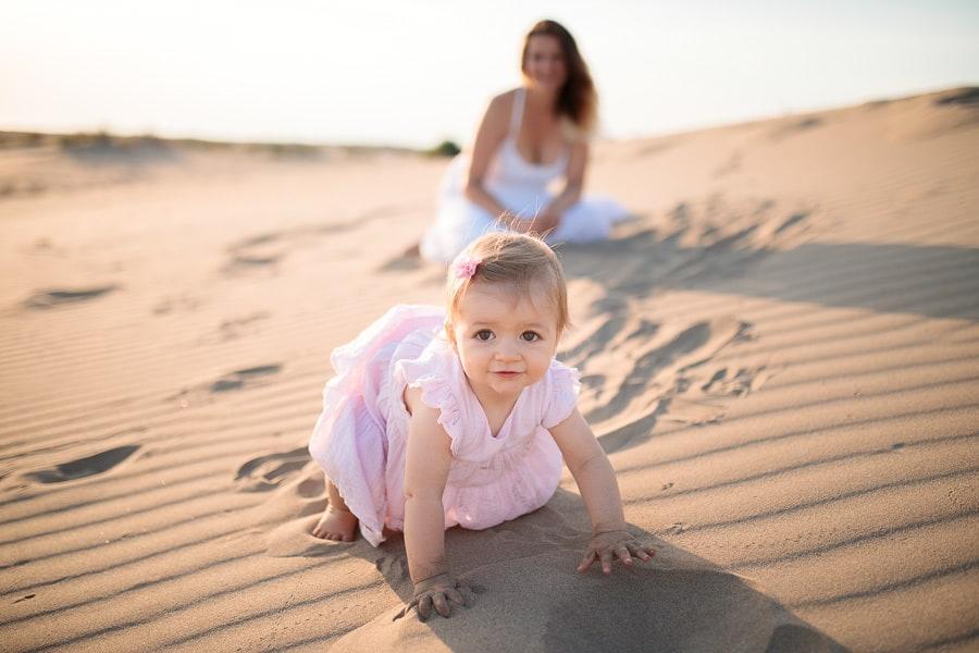 bébé qui marche à quatre pattes dans le sable