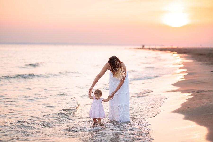 maman et son bébé qui marche au bord de la mer