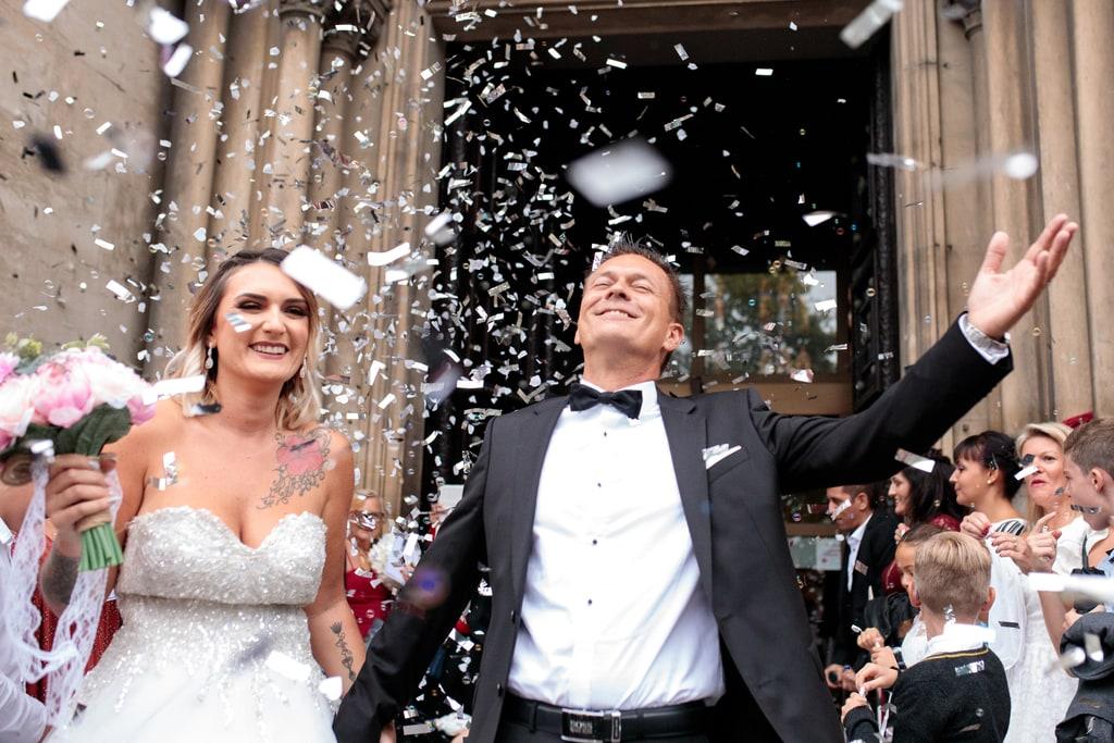 les mariés sortent de l'église avec les confettis