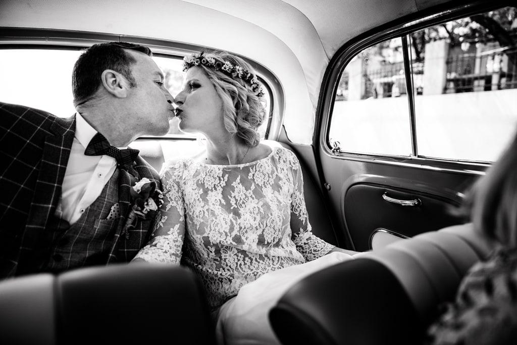 les mariés s'embrassent dans la voiture