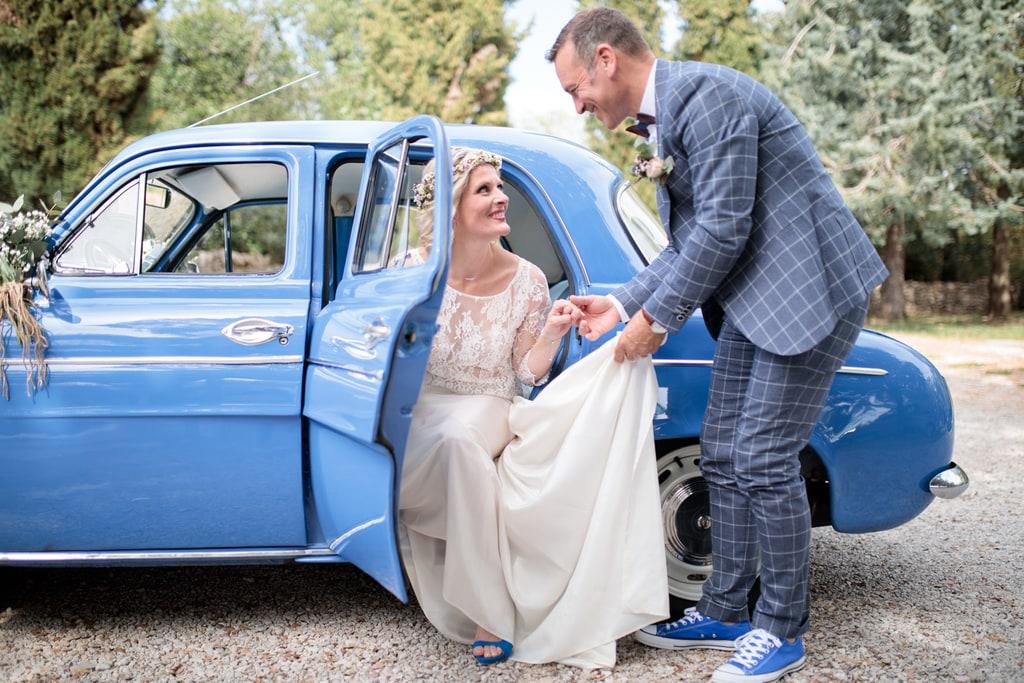 le marié aide la mariée à sortir de la voiture
