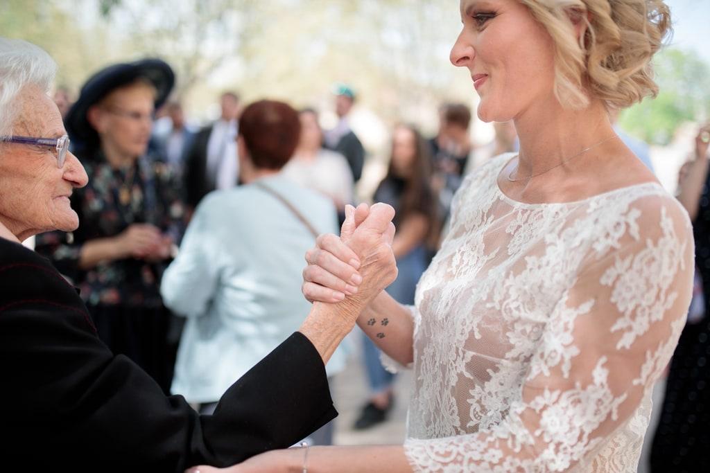 la mariée tient la main de sa grand mère