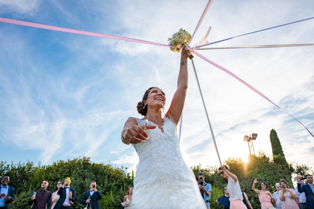 la mariée et le jeu du ruban pour son bouquet