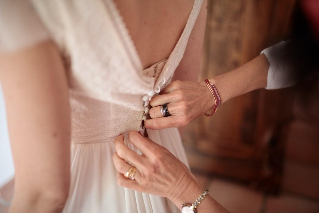 maman ferme les boutons de la robe de sa fille