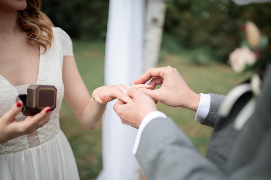 le marié glisse l'alliance sur la main de la mariée
